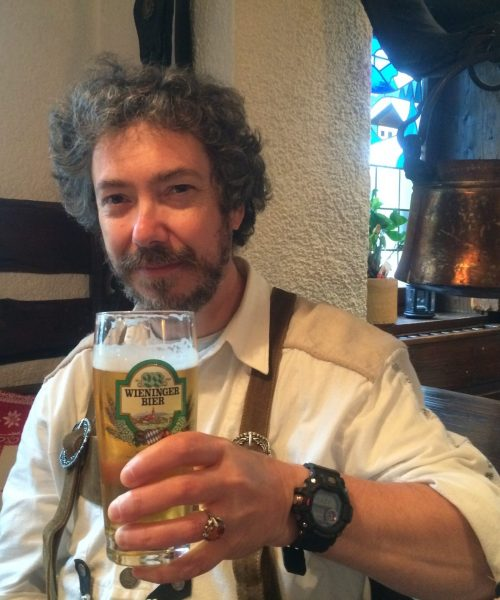 Young man in traditional Austrian clothing raising glass of beer