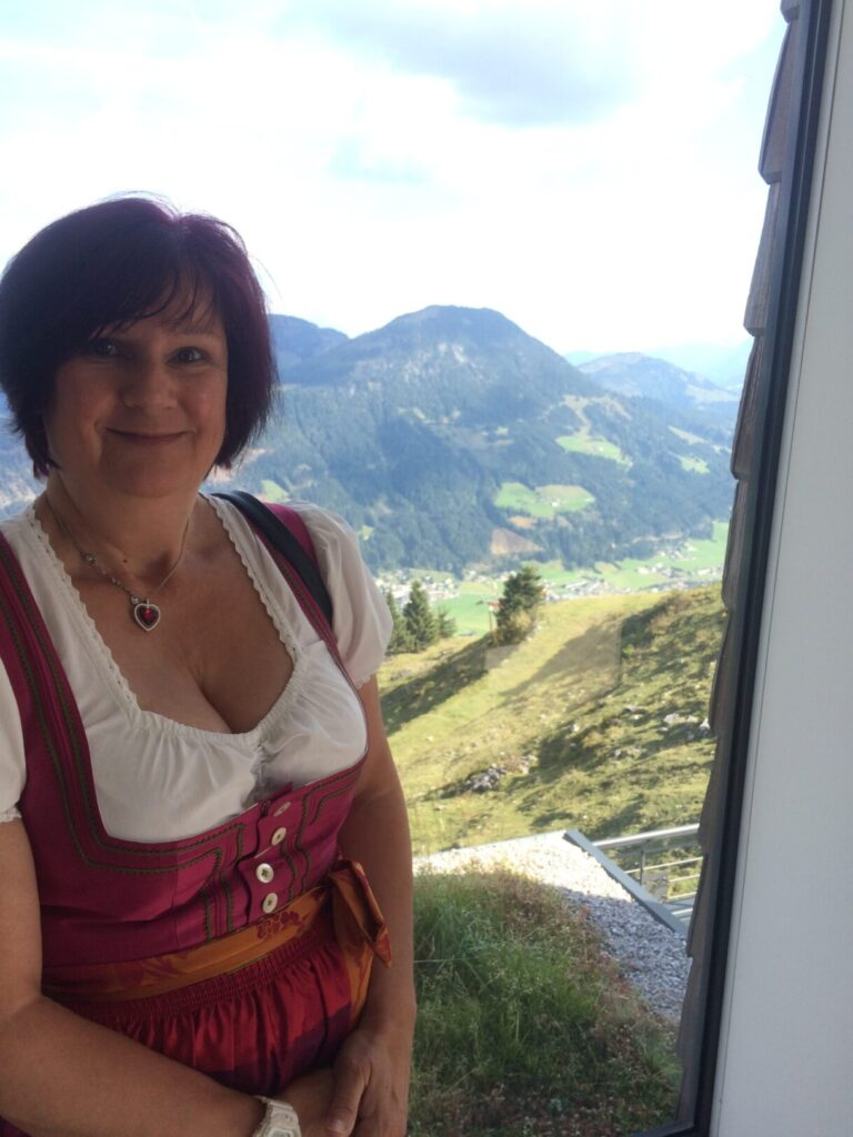 Attractive lady dressed in dirndl leaning against side with mountains in the background