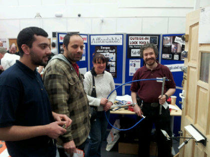 Locksmiths stand watching a demonstration of Locksmiths tools at the Outside-In Lock Tools trade stand at a Show