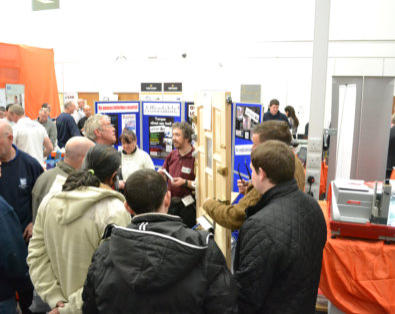 Many people stand crowded around the Outside-In Lock Tools trade stand at a Locksmiths Show