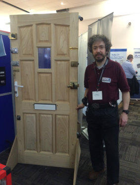 Simon stands by the side of the test door for Locksmiths to use at the Outside-In Lock Tools trade stand