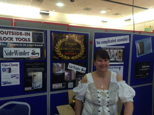 Wendy stands smiling at a Locksmiths Trade Show with various posters in the background