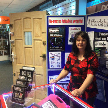 Wendy stands behind the counter at a Locksmiths Show for Locksmiths Tools with the test door in the background