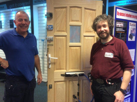 A Locksmith stands smiling beside the test door while Simon stands opposite