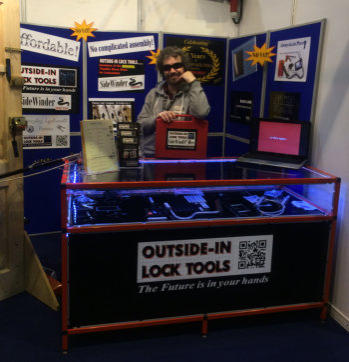 Simon of Outside-In Lock Tools stands behind the counter at a Locksmiths Trade Show while leaning on a tool case