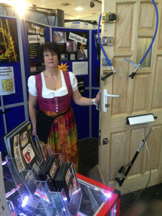 Wendy stands at the side of a test door with Locksmiths tools at a Locksmiths Trade Show
