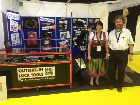 Simon and Wendy of Outside-In Lock Tools stand to the side of their counter at a Locksmiths Trade Show