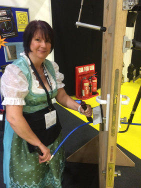 Wendy in a dirndl looks into the camera while she is holding a SideWinder Evolution Locksmiths tool while standing next to a test door.