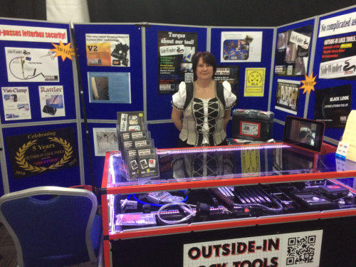 Wendy stands behind the Outside-In Lock Tools stand at a Locksmiths trade show
