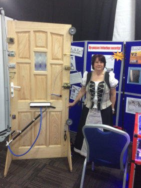 Wendy stands beside the Locksmiths test door at the Outside-In Lock Tools trade stand at a Locksmiths Show