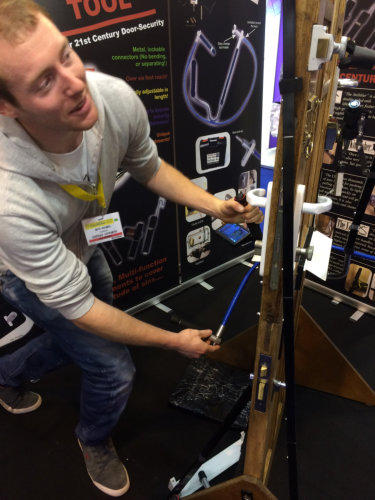 Locksmith using the SideWinder Evolution tool on a test door at a Trade Show