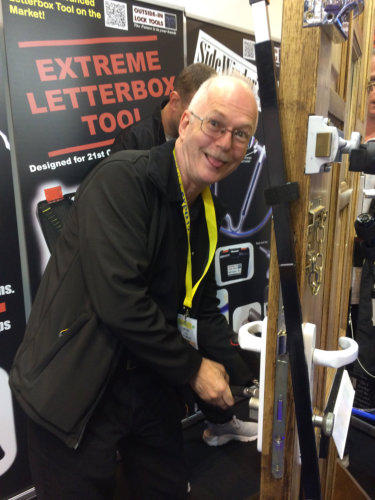 Locksmith smiles as he faces the camera while using an Outside-In Lock Tool through the letterbox of the test door at a trade show