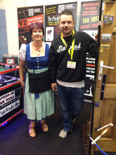 Wendy and a Locksmith stand side by side beside a test door at a Locksmiths Trade Show