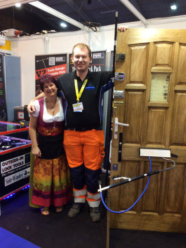 Tall Locksmith in orange trousers stands next to Wendy and also beside the test-door which has an Outside-In Lock Tool in view at a Locksmiths Trade Show