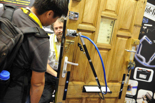 A Locksmith leans over partially behind a test-door filled with locks and uses a tools to open the locks while another Locksmith looks on