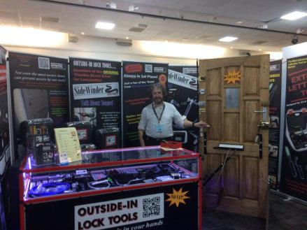 Locksmiths standing behind counter and beside Test door at Locksmiths Trade Show