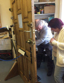 Locksmith trying out tools on test door at a training session while Wendy watches