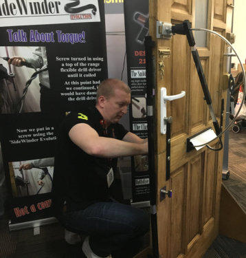 Locksmith using letterbox tool while crouching down by test door at trade show