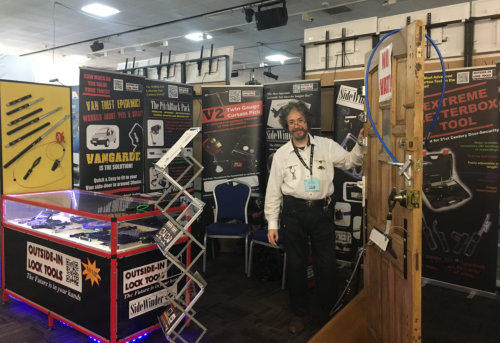 Man standing next to test door and partially behind counter at a Locksmith Trade Show