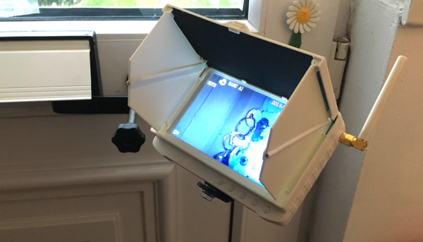 Inside of a door with Monitor bracket through the letterbox and white monitor with sunshade attached