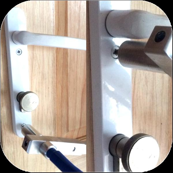 White metal door handle on inside of wooden door showing close-up of screws being removed using Locksmiths tool