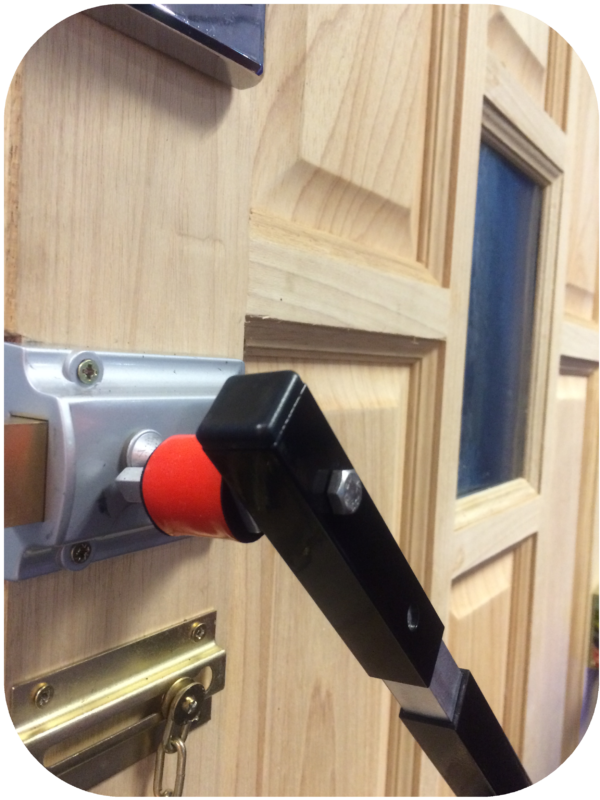Black metal locksmiths tool with bright red cylindrical section in use on the inside of a door