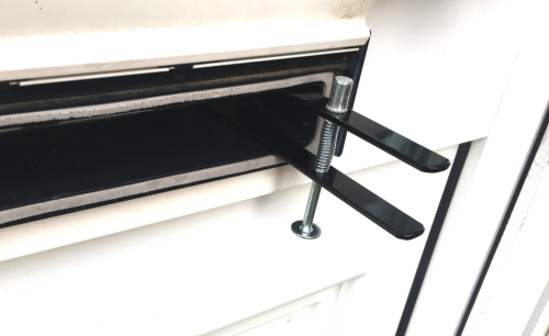 Close-up of letterbox in a white upvc door with black metal device and silver bolt and spring clamp through the letterbox